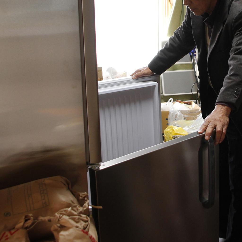 冷蔵庫を開ける土田雅穂さんと米袋