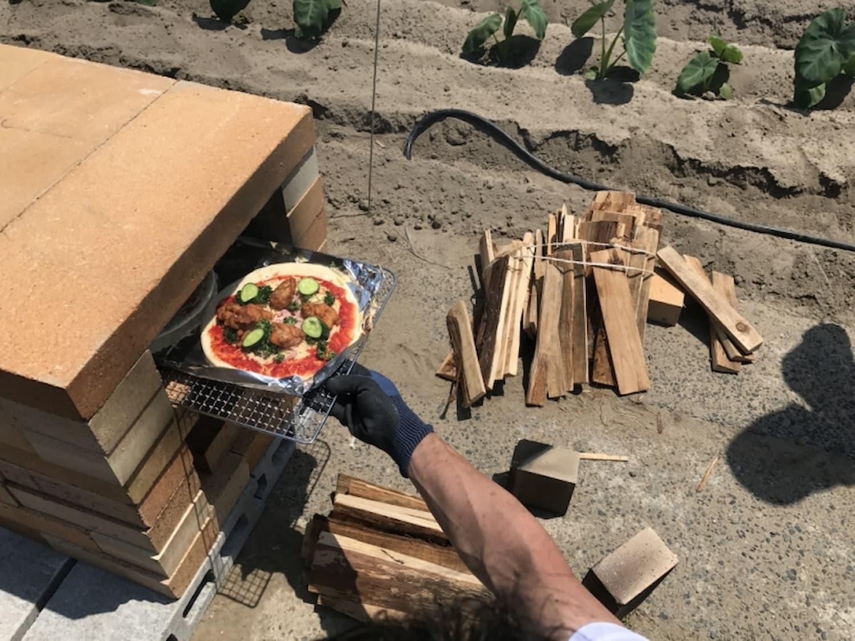 ブロックを積んで作った窯でピザを焼く。とれたての野菜をトッピング。